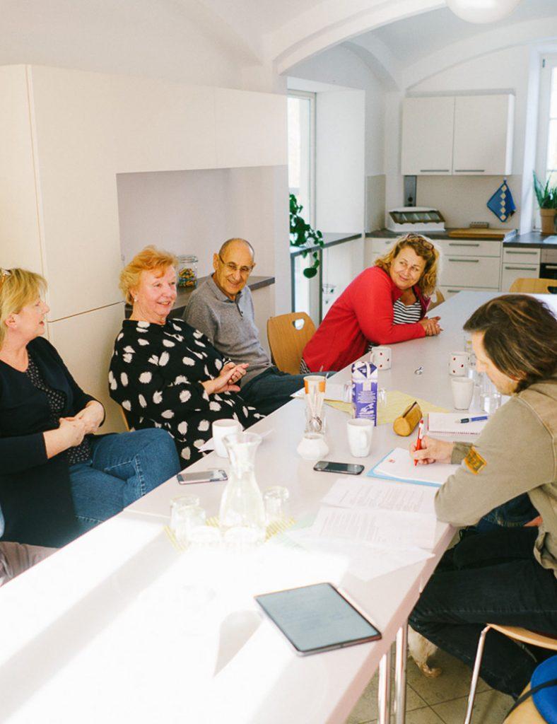 Der Gemeinschaftsraum im Mehrgenerationen-Wohnprojekt Windach. Der Raum ist großzügig und stilvoll in hellen Farben eingerichtet. Sechs Bewohner sitzen zusammen am großen Tisch und tauschen sich angeregt über Neuigkeiten aus.