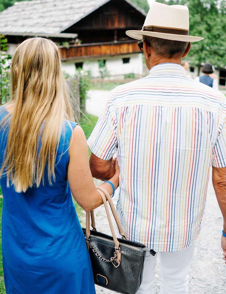 Junge blonde Frau im Sommerkleid geht bei einem älteren Mann mit Sommerhut eigehakt, vom Betrachter weg.