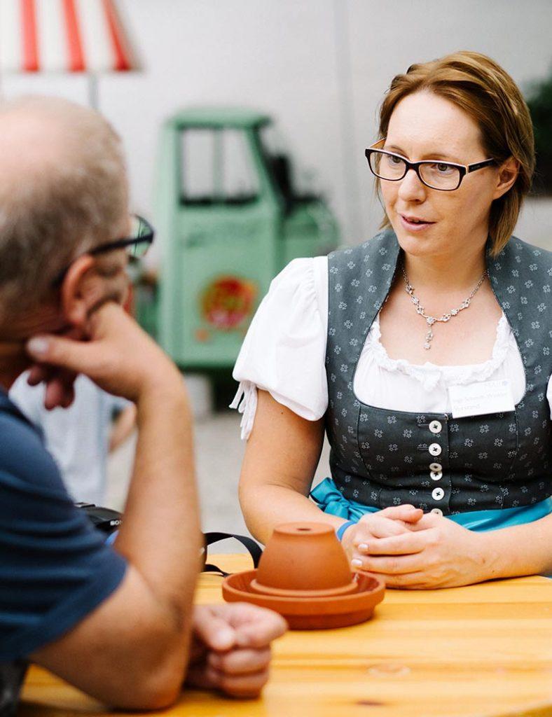 1. Vorständin Inge Schmidt-Winkler sitzt im Freien am Holztisch und spricht mit einem Mann.