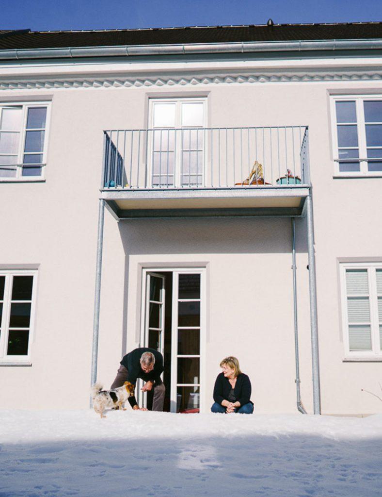 Mann und Frau mit Hund auf zugeschneiter Terrasse im Mehrgenerationen-Wohnen Windach.