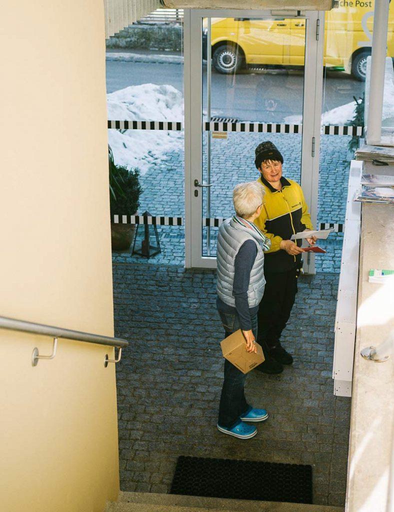 Hausflur des Mehrgenerationen-Wohnprojekts Windach. Bewohnerin und Postbotin treffen an den Briefkästen zusammen.