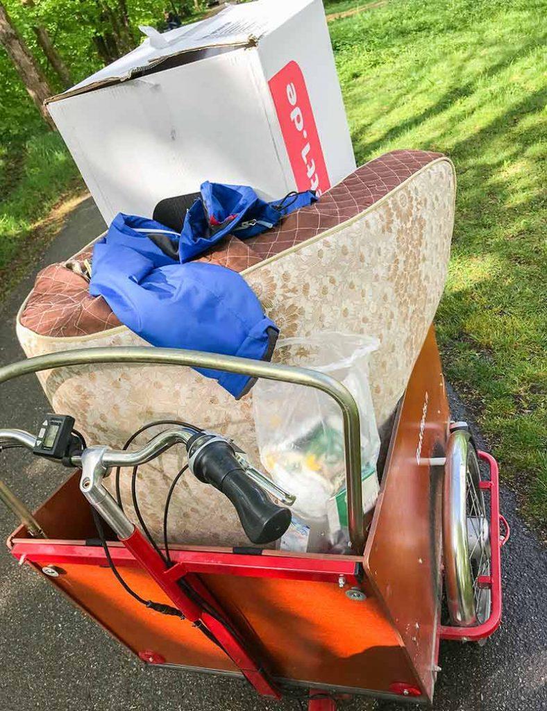 Elektro-Lasten-Rad, beladen mit Matratze und Umzugskarton.