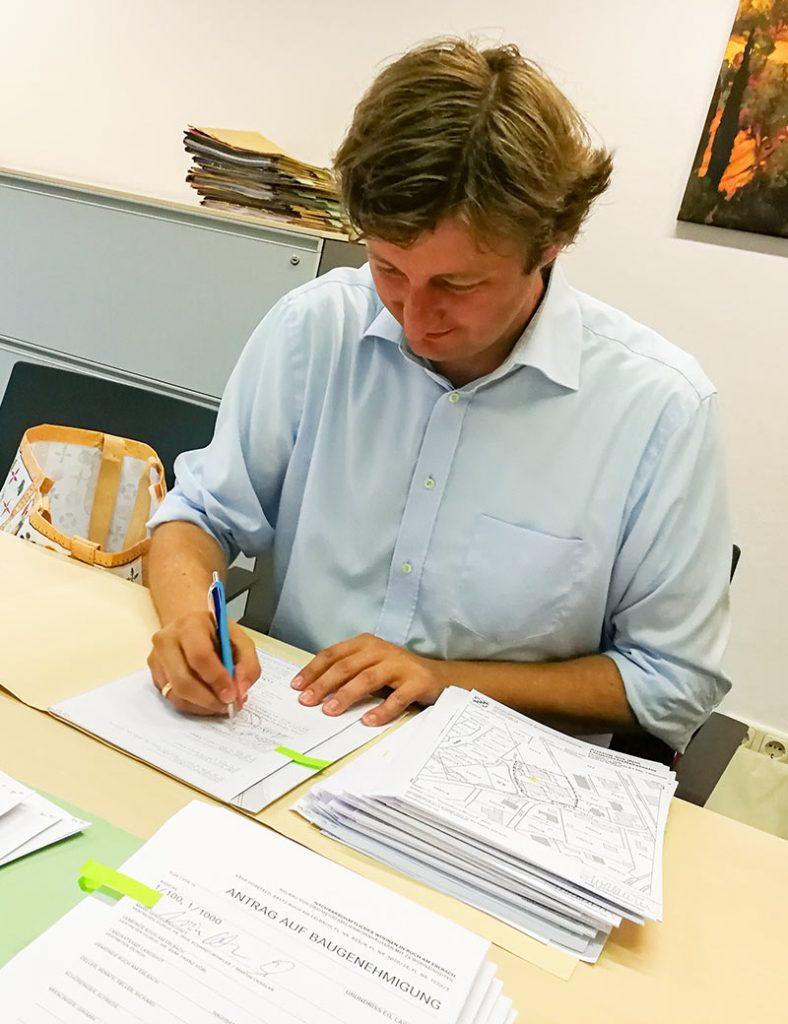 Vorstand Martin Okrslar unterschreibt Kaufvertrag für Buch am Erlbach.