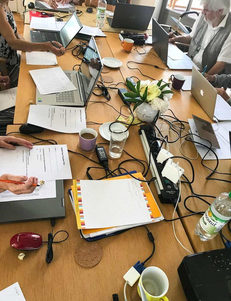 Ein Arbeitstisch voll mit Laptops, Papieren und Getränken.