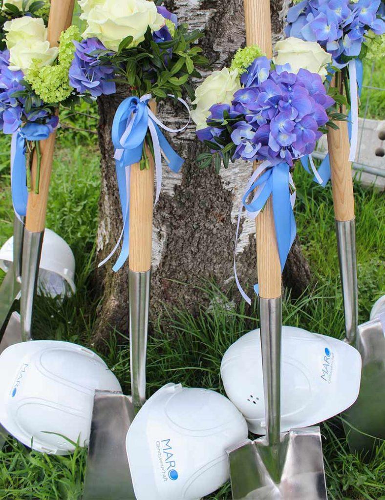 5 Spaten mit Blumenschmuck stehen am Baumstamm angelehnt. Im Gras liegen Bauhelme mit MARO-Aufschrift.